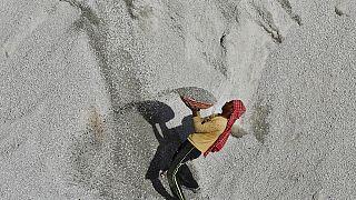Hindistan'da inşaata kum götüren bir işçi.
