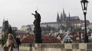 A woman wearing a face mask walks across the medieval Charles Bridge in Prague.