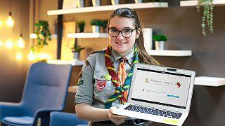 Nella foto, Krysia Paszko vestita con la sua uniforme da boy scout mentre mostra la finta pagina di cosmetici da lei creata