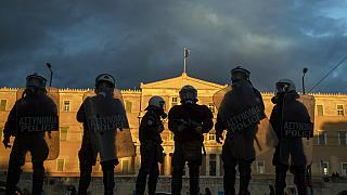 Riot police stand guard in front of the Greek parliament in central Athens
