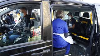 Dr Tamara Joffe prepares to give a Covid-19 jab to Leslie Reid in the back of a London Taxi cab during the pilot project of pop up vaccination drive 'Vaxi Taxi'.