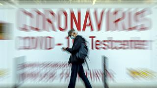 FILE PHOTO: A man walks by a sign in the window of a Coronavirus testing center in Frankfurt, Germany, Thursday, Feb. 25, 2021.