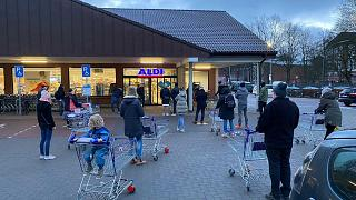 Customers wait for the opening of a branch of the German discounter 'Aldi' in Hamburg, Germany, Saturday, March 6, 2021.