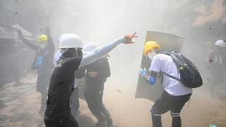Protesters react after tear gas is fired by police during a demonstration against the military coup in Yangon on March 7, 2021.