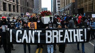 """متظاهرون يحملون لافتات """"لا أستطيع التنفس"""" خلال مسيرة صامتة من أجل العدالة"""" أمام مركز حكومة مقاطعة هينيبين في 7 مارس 2021."""