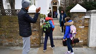 Children are dropped off by their parents at Southbank International School in London on March 8, 2021 as schools reopen.