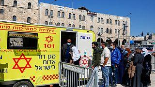 فلسطينيون يصطفون للحصول على لقاح ضد فيروس كورونا خارج عيادة متنقلة.