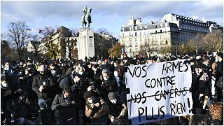 """امرأة تحمل لافتة كتب عليها """"سلاحكم ضد  كاميراتنا لا يجدي نفعا """" خلال مسيرة احتجاجية على مشروع قانون الأمن العالمي  الذي يسعى للحد من تصوير ضباط الشرطة/ ساحة تروكاديرو بباريس"""