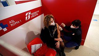Un operatore sanitario somministra una dose di vaccino AstraZeneca a una donna, in un centro di vaccinazione allestito alla stazione Termini di Roma