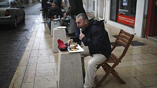 People lunch outside a pizza restaurant in Marignane, southern France, Monday Feb.1, 2021