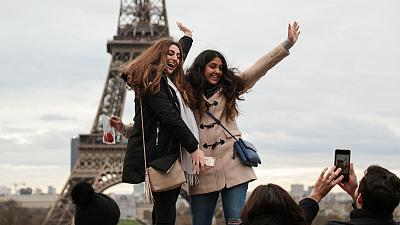 Young people pose for pictures in front of Paris' Eiffel Tower.