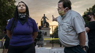 Anais, 26 anni, si batte per la rimozione dell'Emancipation Memorial di Lincoln Park, Washington DC. Accanto a lei, un uomo che la pensa all'opposto