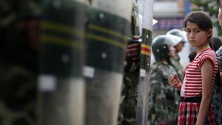 فتاة من الإيغور أمام عناصر من قوات الأمني الصينية المنتشرة في مدينة أورومتشي بمقاطعة شينجاينغ