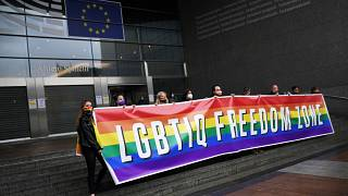 Activists hold a rainbow banner in front of the European Parliament in Brussels on Tuesday ahead of the debate.