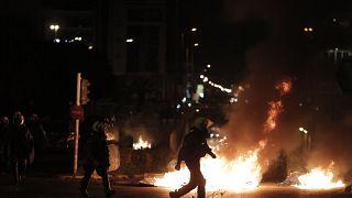 Αστυνομικός των ΜΑΤ περπατάει μπροστά από φωτιές