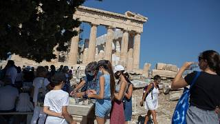 Tourists fill up their water bottles, in front of the ancient temple of Parthenon at Acropolis Hill, in Athens, July 31, 2020.