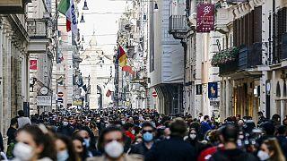 People crowd Via del Corso shopping street in Rome
