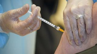 A health worker administers a dose of the AstraZeneca vaccine against COVID-19 to a patient in Rome, Italy on March 10, 2021.