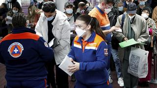 Members of Civil Protection check air travellers documents at Paris Charles de Gaulle airport in Roissy, near Paris, Friday Feb.5, 2021.