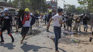 Anti-coup protesters retreat from the frontlines after riot policemen fire sound-bombs and rubber bullets in Yangon, Myanmar, Thursday, March 11, 2021.