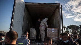 عمال فلسطينيون يفرغون شحنة لقاح Sputnik V الأولى عند وصولها إلى قطاع غزة، 21 فبراير 2021.