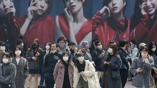 People wearing face masks to protect against the spread of the coronavirus wait at an intersection in Tokyo, Tuesday, March 9, 2021. (AP Photo/Koji Sasahara)