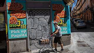 Archivo. Un hombre pasa por delante de un comercio cerrado. Madrid, España