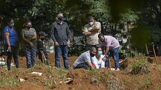 Brezilya'nın  Sao Paulo kentinde Covid-19 nedeniyle yaşamını yitiren bir kişinin yakınları, mezarı başında göz yaşı döktü