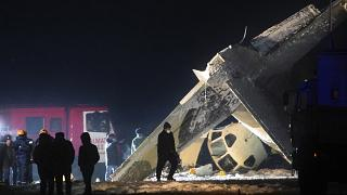 Emergency employees work at the side of the crashed Soviet-built An-26 two-engine turboprop at the airport of Kazakhstan's largest city, Almaty, Kazakhstan.