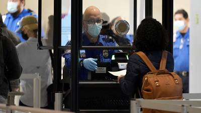 A TSA agent assists a traveller at a security checkpoint at Love Field Airport, Dallas, 24 Nov 2020
