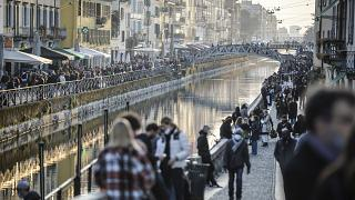 People stroll in the Navigli popular area Milan, Italy, Saturday, March 13, 2021.