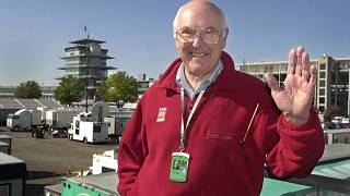 In this Sunday, Sept. 30, 2001 file photo, Legendary Formula 1 race broadcaster Murray Walker poses in the television compound at Indianapolis Motor Speedway.