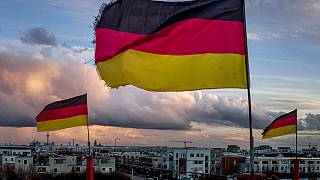 German flags wave in the wind on poles of a small circus in Frankfurt, Germany, March 13, 2021.