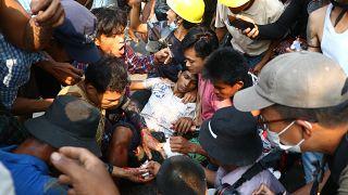 Des manifestants opposés au coup d'État entourent un homme blessé à Rangoun le 14 mars 2021.