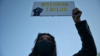 A protestor brandishes a portrait of Breonna Taylor during a rally in remembrance on the one year anniversary of her death in Louisville, Kentucky on March 13, 2021.
