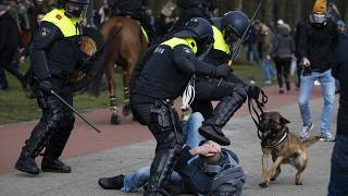 Dutch riot police kick a man during a demonstration to protest government policies including the curfew, lockdown and coronavirus related restrictions in The Hague.