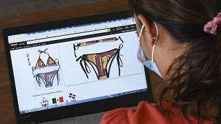 سيدة تنظر إلى لباس بحر نقش عليه علم سريلانكا على موقع أمازون