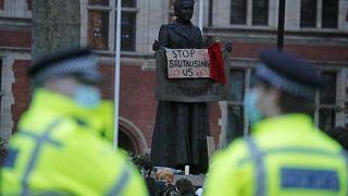 ضابشا شرطة ينظران إلى لافتة معلقة على تمثال ميليسنت غاريت الداعمة لحقوق المرأة خلال تجمع متظاهرين في لندن. 2021/03/14