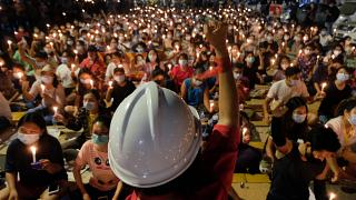 An anti-coup protester raises his hand with clenched fist in front of a crowd during a candlelight night rally in Yangon, Myanmar Sunday, March 14, 2021.