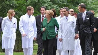 المستشارة الألمانية أنغيلا ميركل تتحدث مع الأطباء أثناء زيارتها لمستشفى سانا في كرمن- شمال شرق ألمانيا.