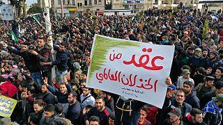 """تظاهرة بذكرى اندلاع """"الثورة السورية"""" في إدلب ولافتة مكتوب عليها عقد من الخذلان العالمي"""