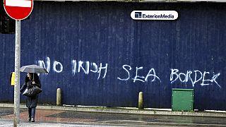 A woman walks past past graffiti with the words 'No Irish Sea Border' in Belfast city centre, Northern Ireland, Wednesday, Feb. 3, 2021.