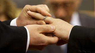 Római pár tagjai húznak jegygyűrűt egymás ujjára élettársi kapcsolatuk bejegyzésekor Rómában 2015. május 21-én