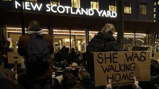 People hold signs outside New Scotland Yard during a march to reflect on the murder of Sarah Everard, in London, March 15, 2021.