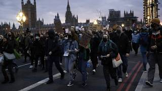 People hold signs as they march across Westminster bridge outside the Parliament during a march to reflect on the murder of 33 year old marketing executive, Sarah Everard.