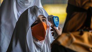 Un membro del personale controlla la temperatura alle  studentesse, che tornano sui banchi di scuola a Srinagar, nel Kashmir controllato dall'India