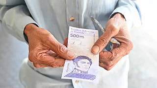 Un hombre muestra un billete de 200.000 bolívares