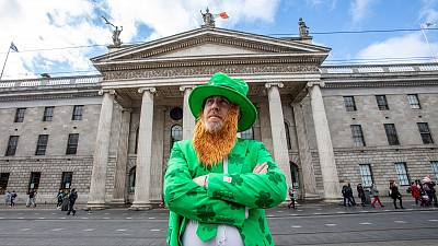 A man celebrating St Patrick's Day poses outside the Genearl Post Office (GPO) in O'Connell Street, Dublin on March 17, 2020, as festivities were cancelled due to COVID
