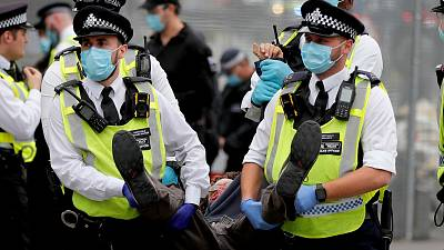 olice officers with face masks carry a protestor away during an Extinction Rebellion climate change protest at Parliament Square in London.