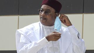 Niger President Mahamadou Issoufou takes off his face mask as he arrives for a group picture during the G5 Sahel summit, June 30, 2020, in Nouakchott.
